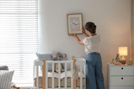 Decorator hanging picture on wall in baby room. Interior design Standard-Bild