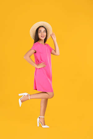 Young woman wearing stylish pink dress on yellow background