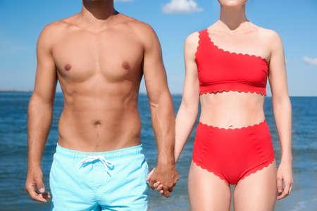 Woman in bikini and her boyfriend on beach, closeup. Lovely couple Foto de archivo