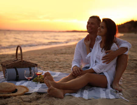 Lovely couple having romantic picnic on beach at sunset