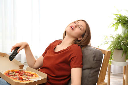 Lazy young woman with pizza and TV remote sleeping at home