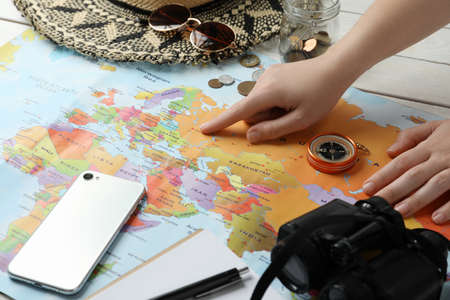 Woman with world map at table, closeup. Travel during summer vacation Standard-Bild