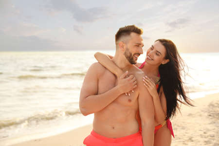Happy young couple on beach on sunny day