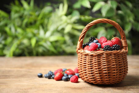 Mix of ripe berries on wooden table. Space for text