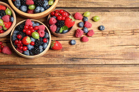 Mix of ripe berries on wooden table, flat lay. Space for text 스톡 콘텐츠
