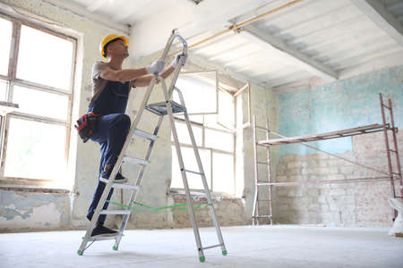 Professional constructor on ladder in old building