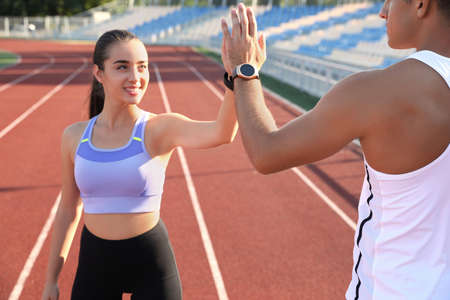 Couple with fitness trackers giving each other high fives after training at stadium 版權商用圖片