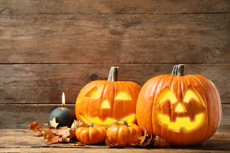 Scary jack o'lantern pumpkins, burning candle and fallen leaves on wooden background. Halloween decor