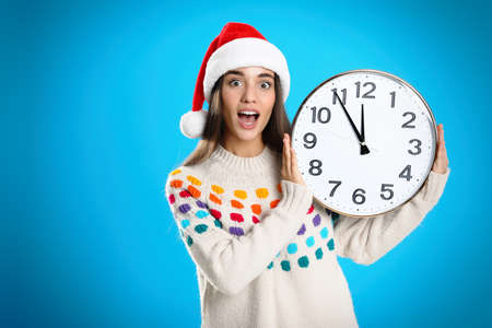 Woman in Santa hat with clock on light blue background. Christmas countdown Stock Photo