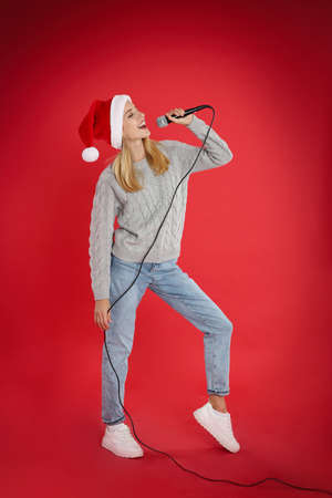 Happy woman in Santa Claus hat singing with microphone on red background. Christmas music