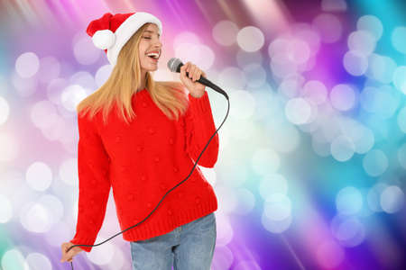 Happy woman in Santa hat singing on bright background, bokeh effect Stock Photo