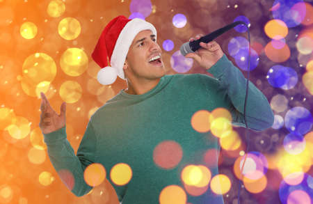 Happy man in Santa hat singing on bright background, bokeh effect