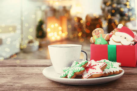 Christmas cookies and cup of hot drink on wooden table in decorated room