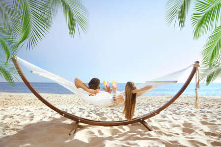 Couple with refreshing cocktails relaxing in hammock under green palm leaves on beach