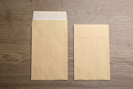 Kraft paper envelopes on wooden background, flat lay