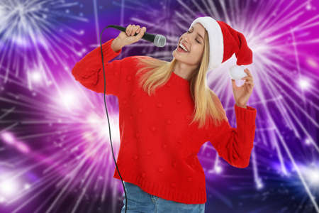 Happy woman in Santa hat singing on bright background
