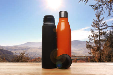 Wooden desk with thermo bottles and mountain landscape on background