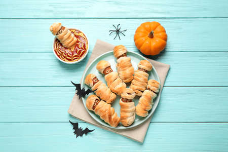 Spooky sausage mummies for Halloween party served on light blue wooden table, flat lay 版權商用圖片