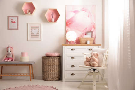Stylish child's room interior with beautiful pictures and chest of drawers