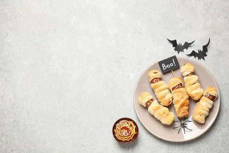 Spooky sausage mummies for Halloween party served on light gray table, flat lay. Space for text