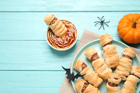 Spooky sausage mummies for Halloween party served on light blue wooden table, flat lay. Space for text