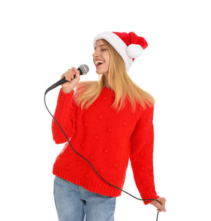 Happy woman in Santa Claus hat singing with microphone on white background. Christmas music Stock Photo