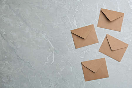 Brown paper envelopes on gray marble background, flat lay. Space for text 版權商用圖片