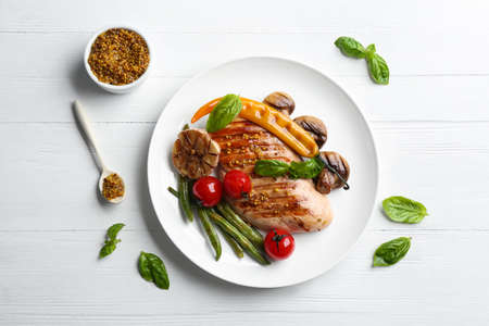 Tasty grilled chicken fillet with mustard and vegetables on white wooden table, flat lay