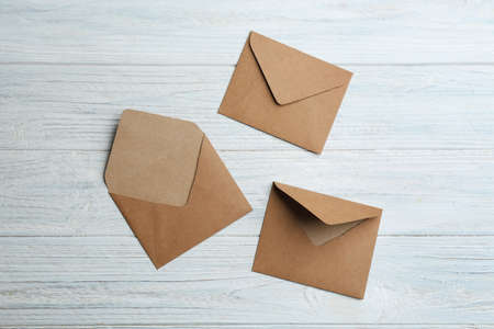 Brown paper envelopes on white wooden background, flat lay