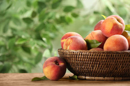 Fresh sweet peaches in wicker basket on wooden table outdoors Standard-Bild