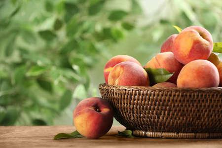 Fresh sweet peaches in wicker basket on wooden table outdoors Stock fotó