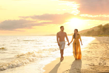 Happy young couple walking together on beach at sunset