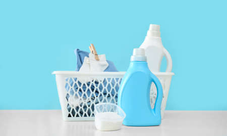 Detergents and children's clothes on white table near light blue wall. Space for text 版權商用圖片