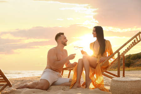 Romantic couple drinking wine together on beach at sunset