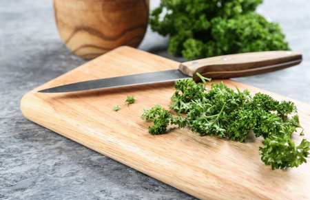 Fresh curly parsley, cutting board and knife on gray table