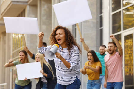 Emotional African American young woman with megaphone at protest outdoors
