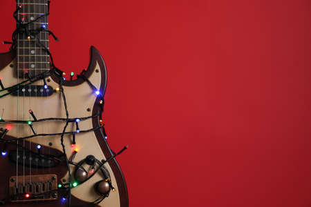 Closeup view of guitar with fairy lights on red background, space for text. Christmas music