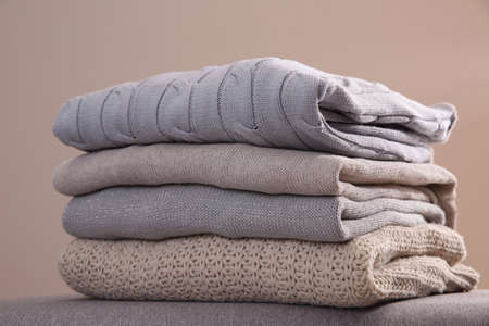 Stack of folded warm sweaters against gray background, closeup Stock Photo