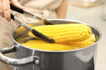 Woman taking boiled corn from pot with tongs in kitchen, closeup Standard-Bild