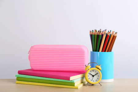 Different school stationery and alarm clock on table against white background. Back to school