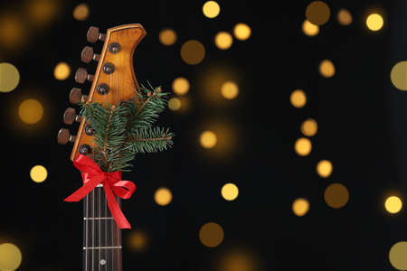 Guitar with bow and fir tree twig against blurred lights, space for text. Christmas music Stock Photo