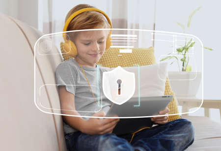 Child safety online. Little boy using tablet at home. Illustration of internet blocking app on foreground