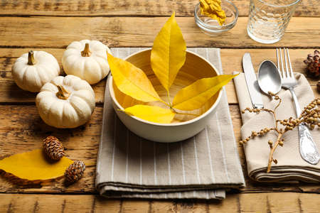 Seasonal table setting with pumpkins and autumn leaves on wooden background
