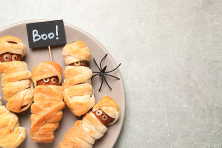 Spooky sausage mummies for Halloween party served on light gray table, top view. Space for text