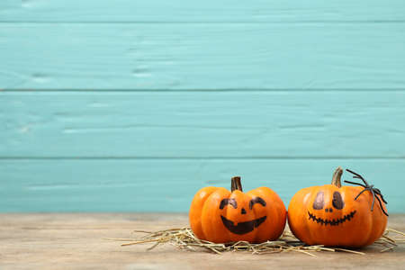 Pumpkins with scary faces on light blue wooden background, space for text. Halloween decor