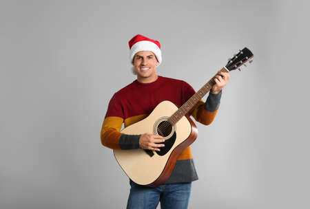 Man in Santa hat playing acoustic guitar on light gray background. Christmas music