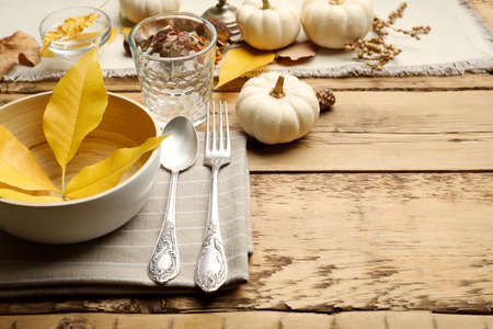 Seasonal table setting with pumpkins and other autumn decor on wooden background. Space for text