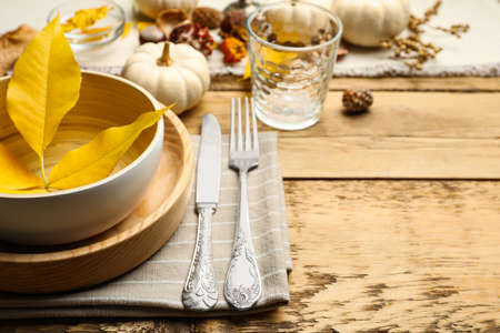Seasonal table setting with pumpkins and other autumn decor on wooden background, closeup. Space for text 免版税图像