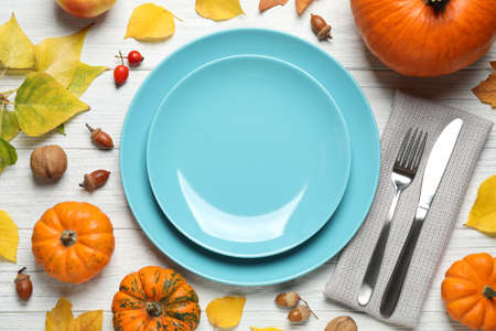Flat lay composition with tableware, pumpkins and autumn leaves on white wooden background. Thanksgiving day 免版税图像