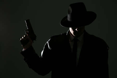 Old fashioned detective with gun on dark background